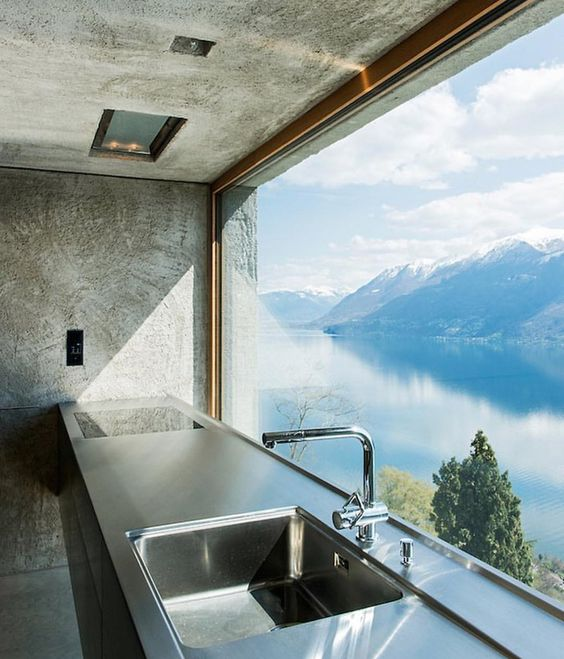 a kitchen with an unframed and uncovered view of a mountain lake inspires to create a culinary masterpiece