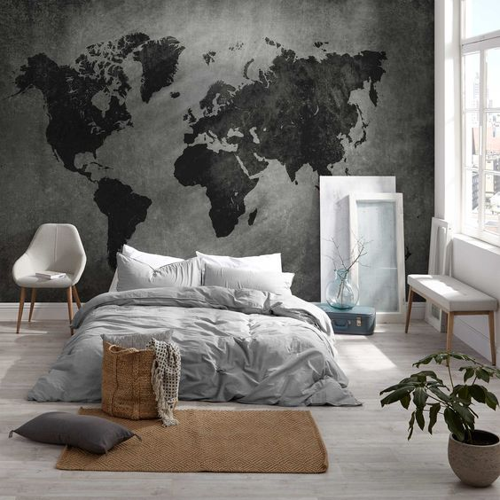 a minimalist bedroom with a dark world map mural as a decor statement in the space