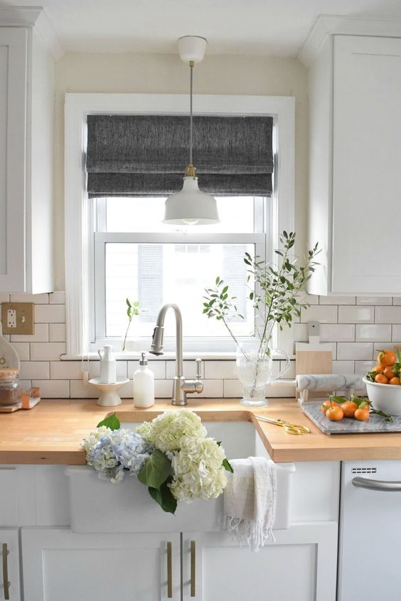 grey Roman shades add a touch of color to the all white kitchen and keep it private when needed