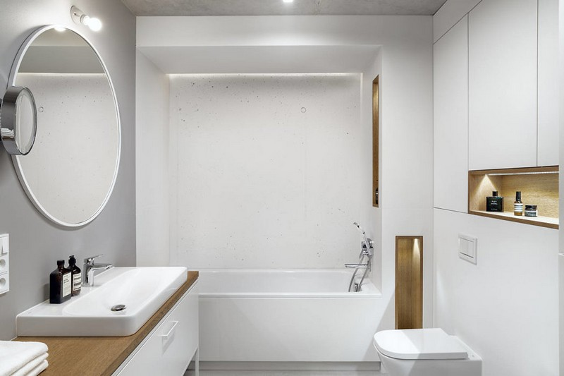 The bathroom is minimal and white, done with sleek surfaces, light wood touches and much storage space