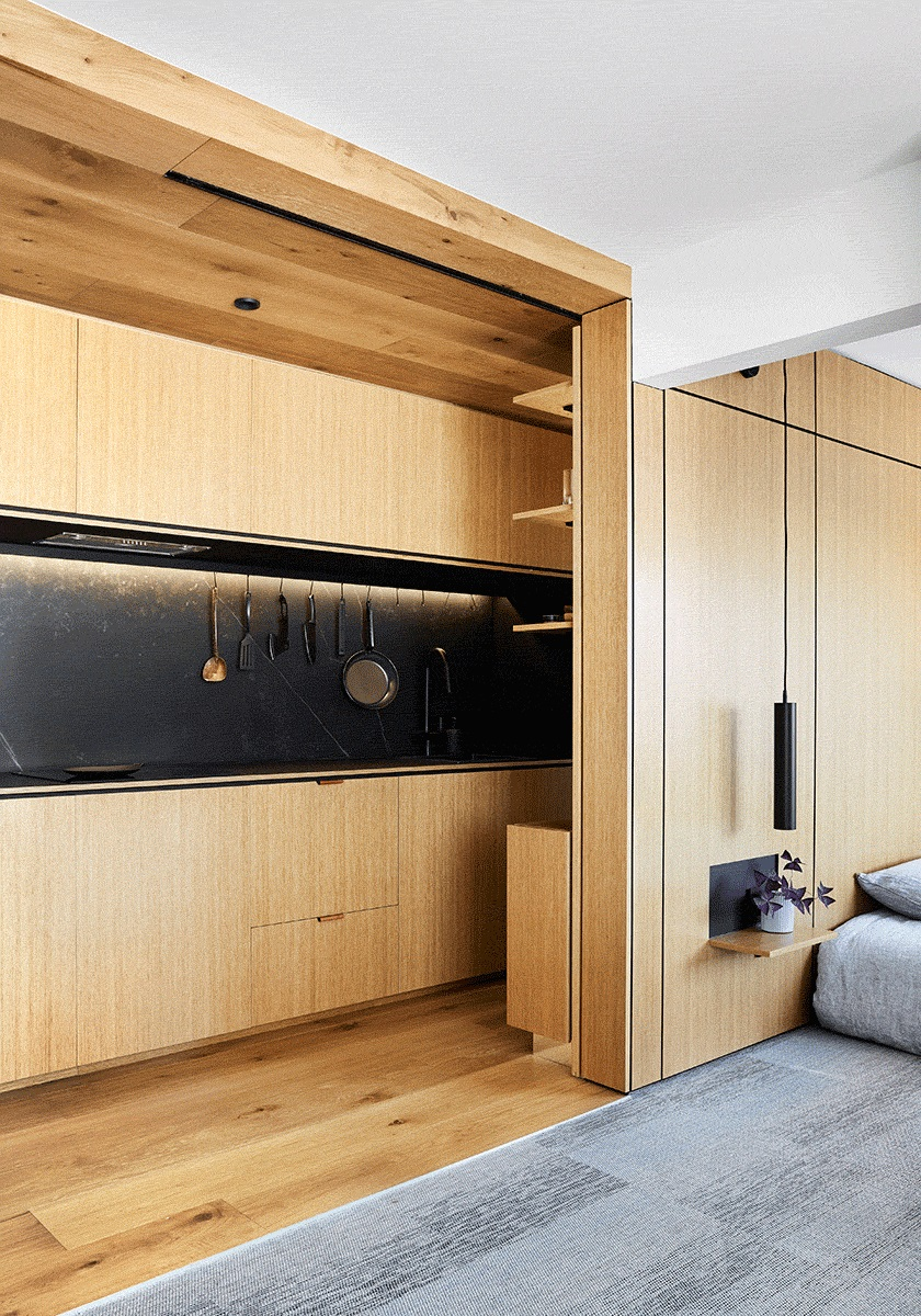 The dining space with a table and stools can be hidden inside the bedroom headboard