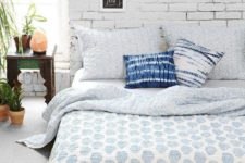 09 a cute boho bedroom with a white brick statement wall that becomes a cool backdrop for little artworks