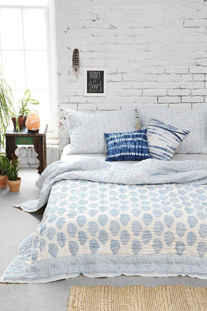 a cute boho bedroom with a white brick statement wall that becomes a cool backdrop for little artworks