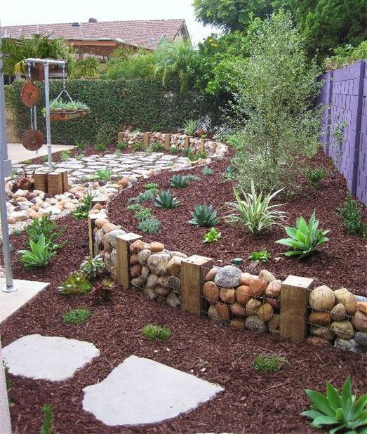 a gabion wall used as garden edging blends with the natural environment making it fresh and cool