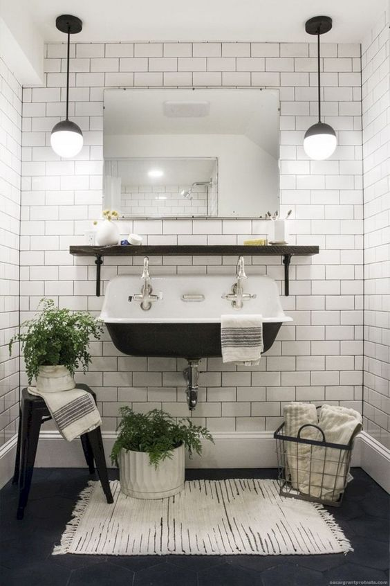 a vintage-inspired powder room in black and white, with white subway tiles with black grout