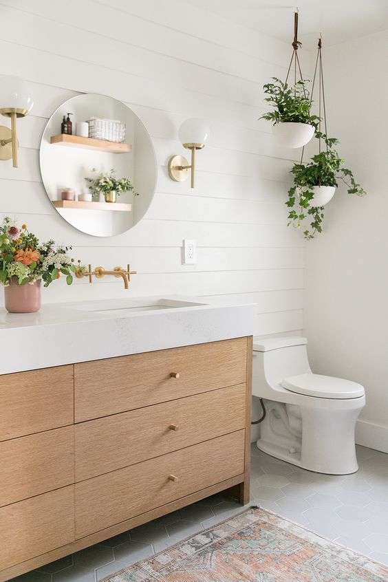 an airy contemporary meets boho bathroom with white shiplap, a light stained vanity, potted greenery and a round mirror