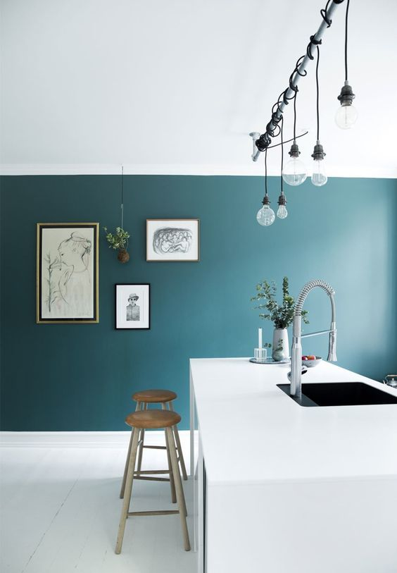 highlight a white ultra-minimalist kitchen with a teal accent wall plus a gallery wall on it