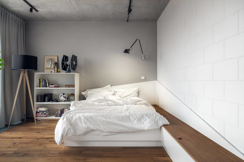 The second bedroom features a unique platform bed, a storage unit, some lamps and concrete