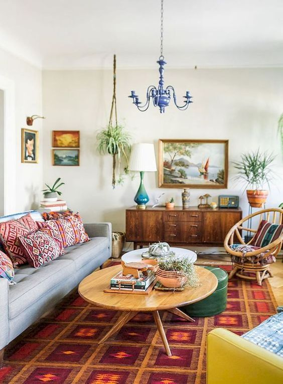 a boho meets mid-century modern living room with bright printed pillows, a rug and colorful furniture