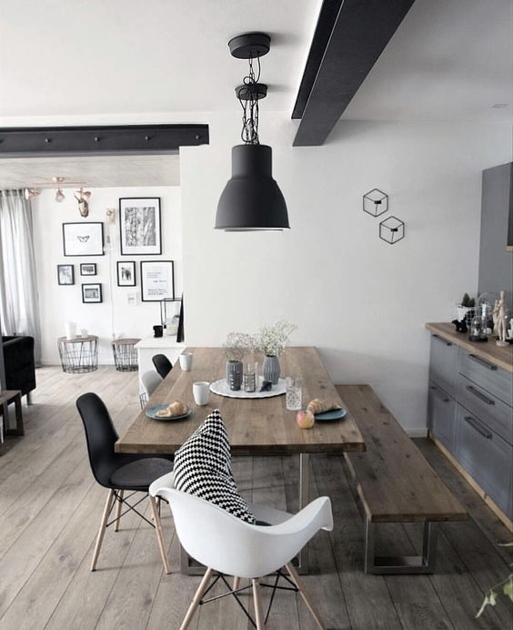 a contemporary dining space with a wooden table and bench plus black and white chairs for a fresh feel