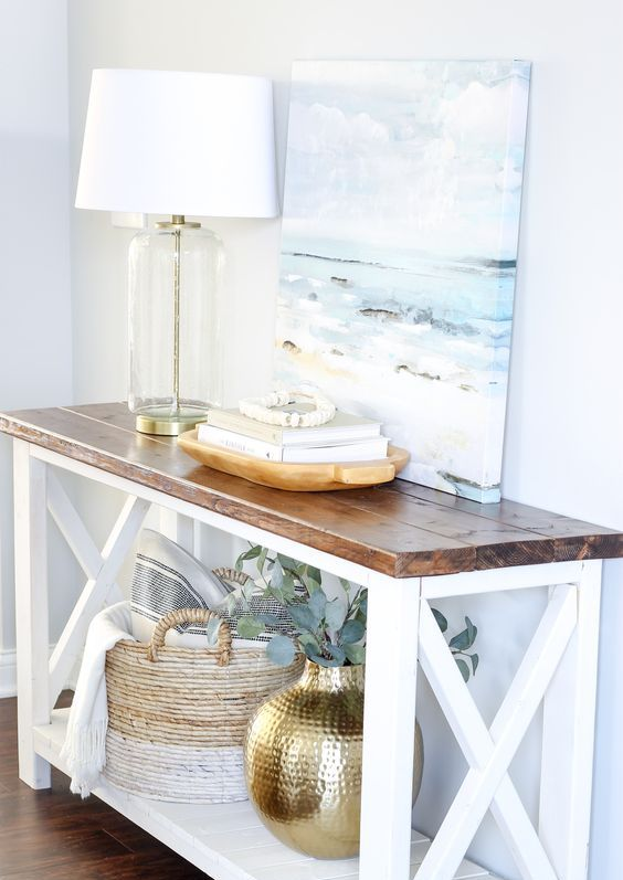 a rustic meets modern console table in white and with a rich stained tabletop for a coastal entryway