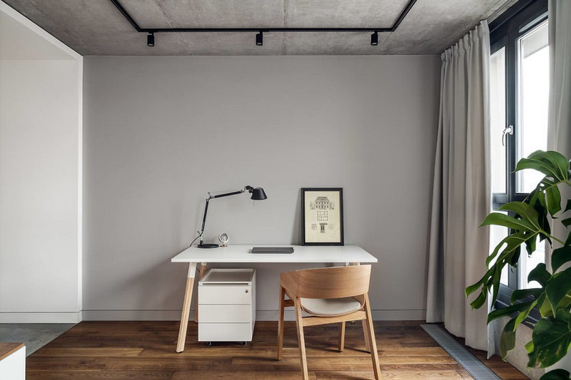 There's also a home office space by the window, with a sleek white desk and a chair