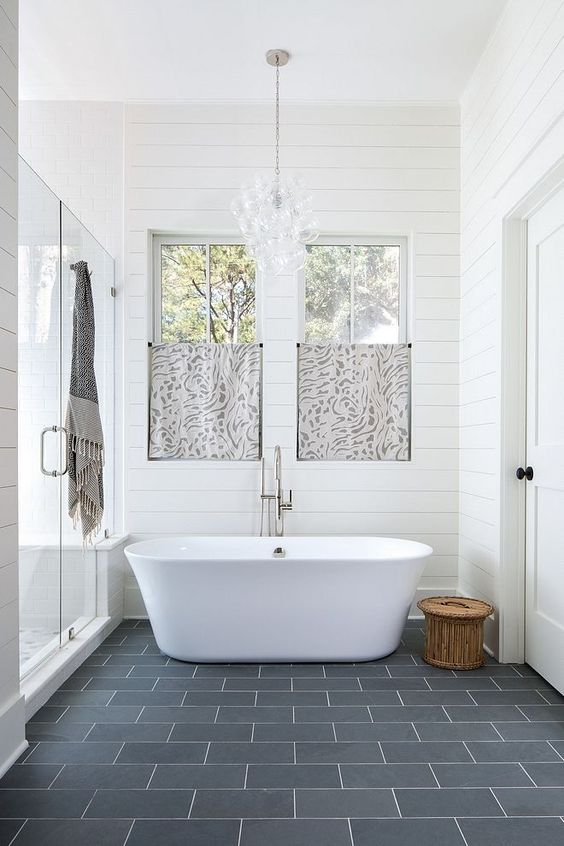 a beautiful master bathroom with shiplap walls, ample natural light, and freestanding soaking tub