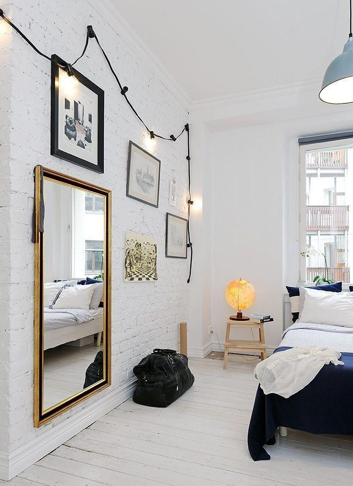 a dreamy Scandinavian bedroom with white brick walls, a whitewashed floor shows off black framed art and dark bedding