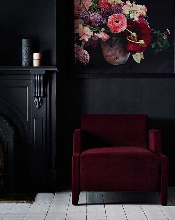 a moody nook spruced up with a bold florla artwork and a burgundy chair for more color