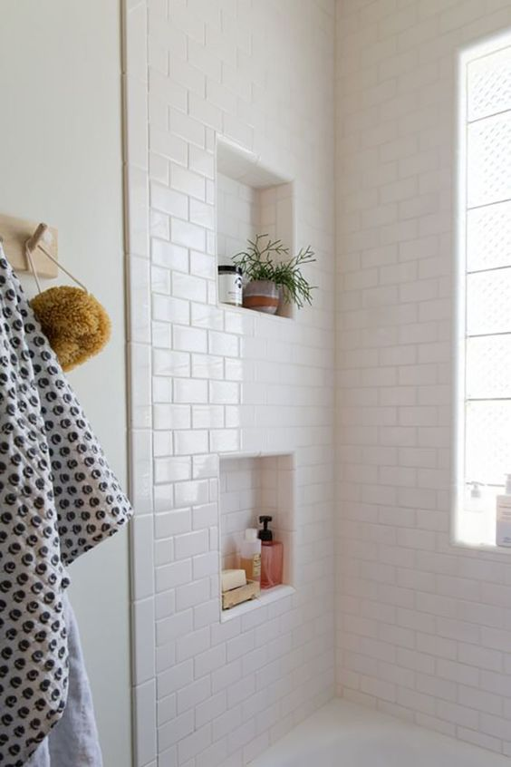 a shower space fully clad with white subway tiles and white grout features niches for storage