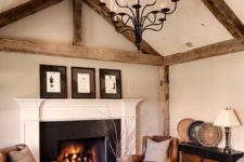 11 a warm-colored living room with brown leather furniture, a warm-colored rug and wooden beams