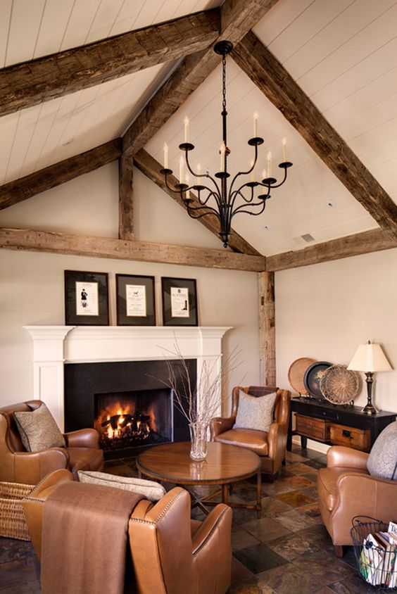 a warm-colored living room with brown leather furniture, a warm-colored rug and wooden beams