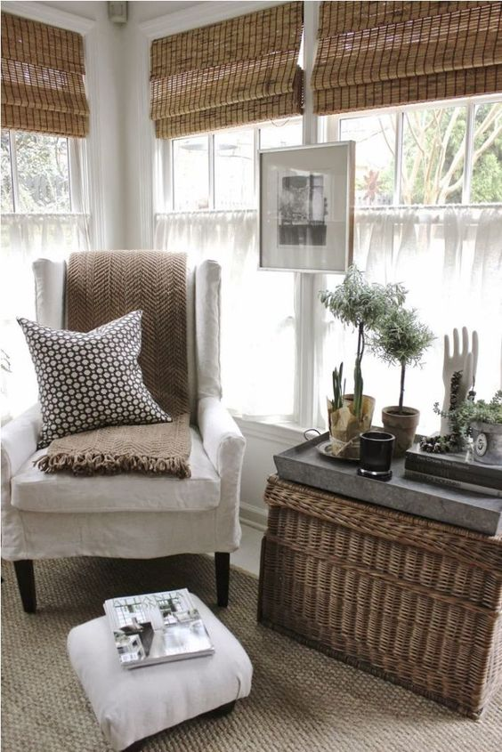 bamboo Roman shades, a basket as a coffee table and potted greenery bring an outdoor feel inside