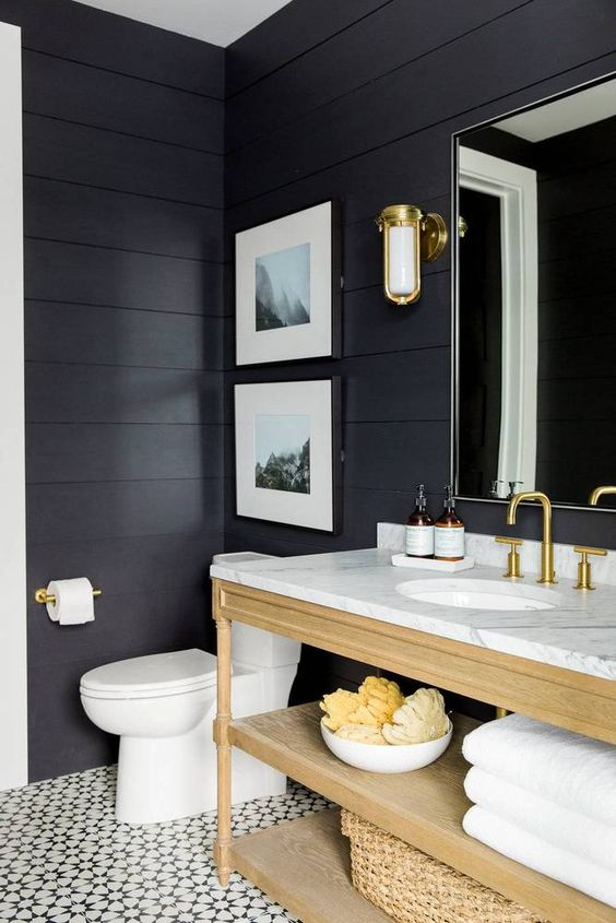 a chic and elegant bathroom with mosaic tiles, black shiplap walls, a light stained vanity and wall candle lanterns