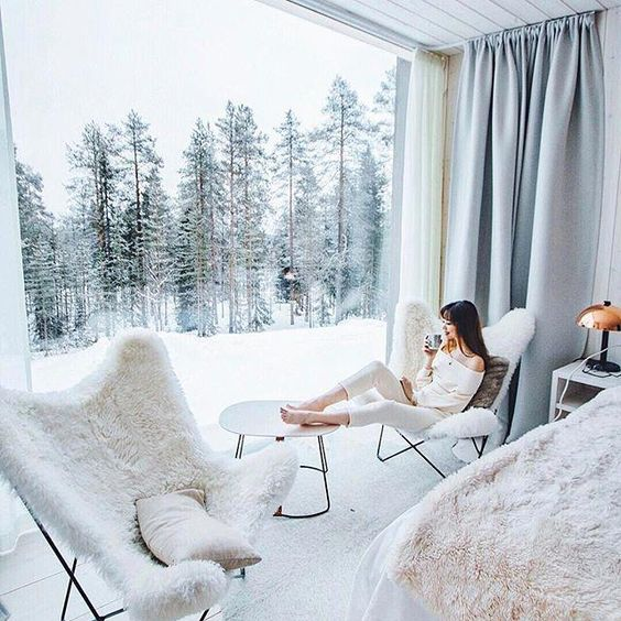 a couple of fur covered chairs, a side table by the glazed wall create a chic space to enjoy the views and breathe in that frosty air