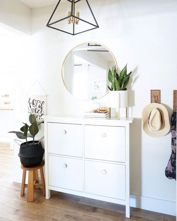 a geometric framed chandelier with brass touches adds chic to the entryway lighting it up