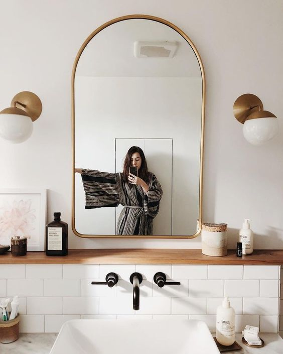 an elegant arched gold frame mirror and matching wall lamps to add chic to your bathroom