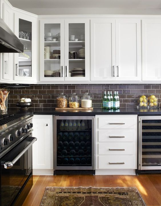 dark chocolate subway tiles with white grout make up a contrasting and bold kitchen backsplash