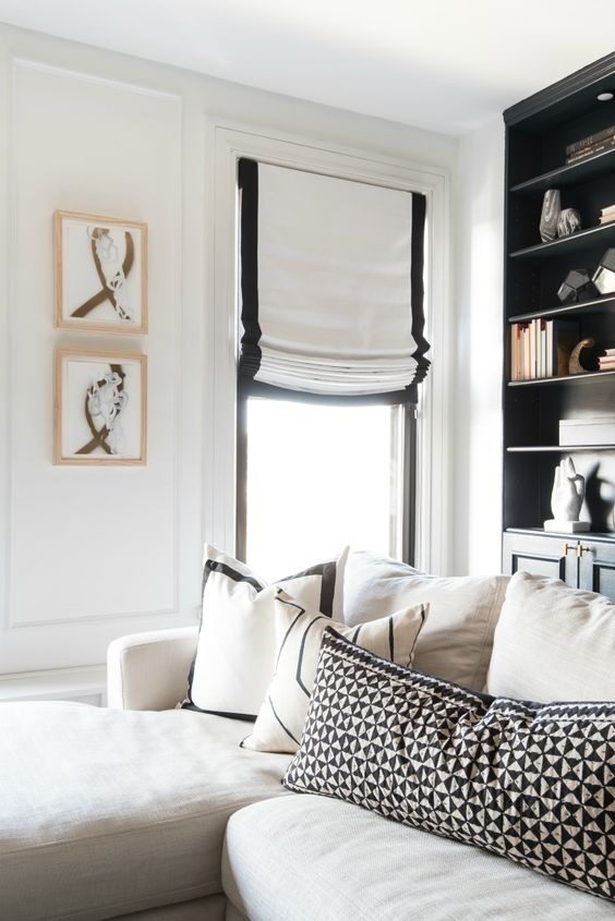 white Roman shades with a black border add chic and interest to the monochromatic living room