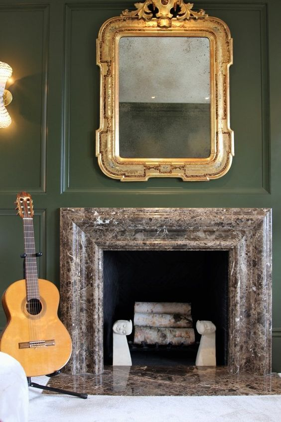 an antique gold mirror on a dark green wall