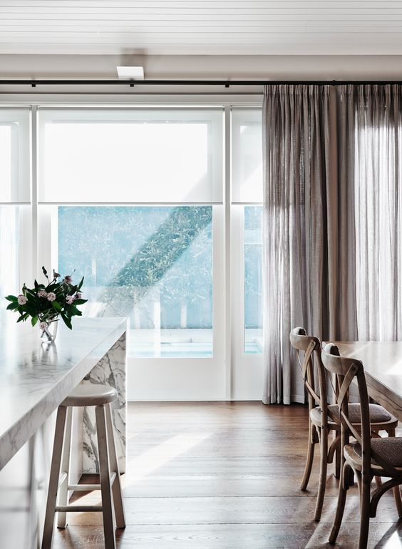 neutral roller shades look very well with curtains of any color and texture blocking excessive light