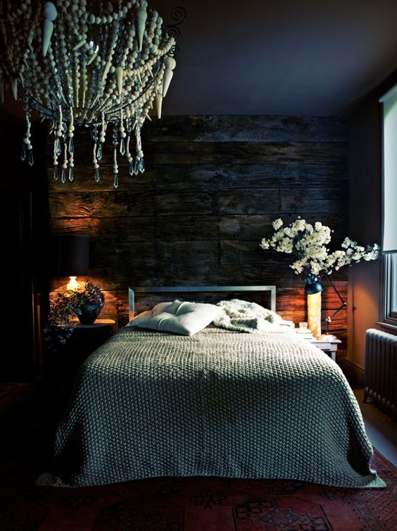 some wall and table lamps in this dark and moody bedroom create a cozy ambience and you'll want to stay here longer
