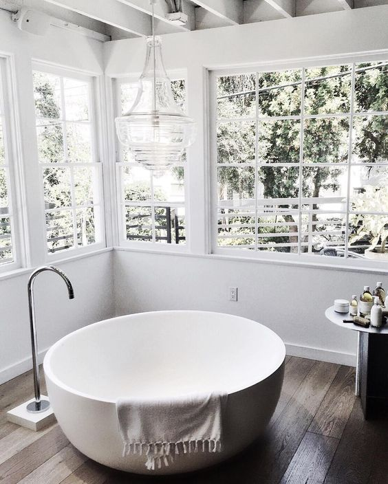a bowl-shaped bathtub placed by the windows to fill this space with light and enjoy the views