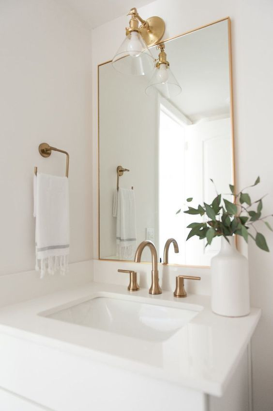 a mirror in a thin gold frame, with gold fixtures and a wall lamp for a stylish and bright bathroom nook