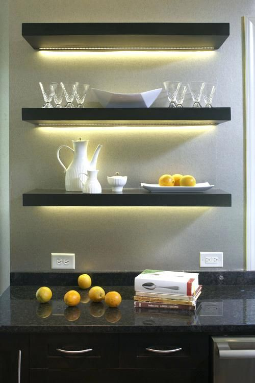 a simple home bar with open shelves highlighted with strip lighting that accent this space a lot