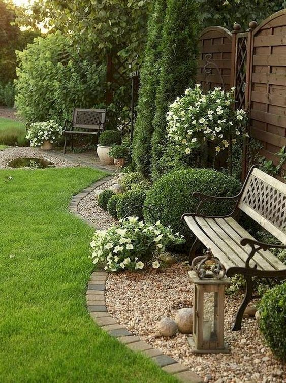 brick edging is timeless, here it divides the lawn and the pebble covered garden bed with a bench