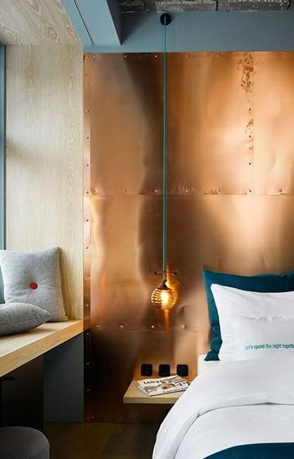 mixing cold and warm hues is a bodl idea, here a copper wall is paired with emerald bedding and grey pillows