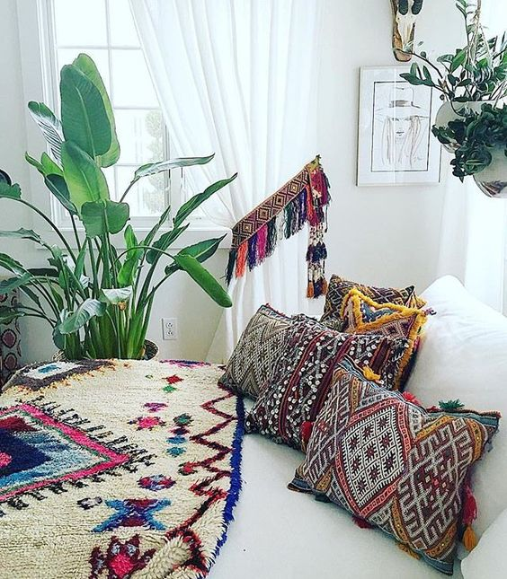 super bold and colorful printed pillows with colorful fringe and a matching curtain holder with tassels for a neutral bedroom