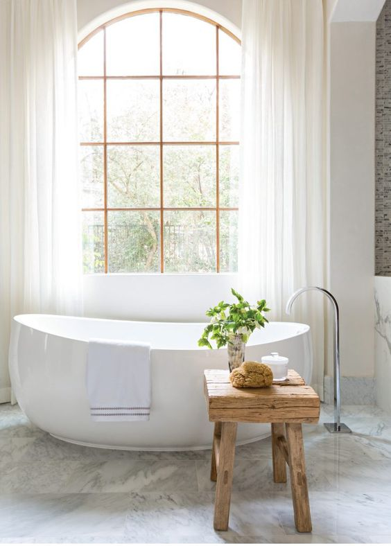 a contemporary bathroom with a free-standing bathtub and a rough wooden stool