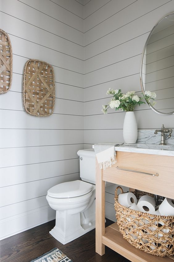 a fresh farmhouse bathroom with off white shiplap, a wooden vanity, decorative baskets and touches of white