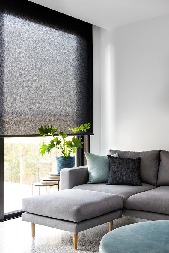 black rolled shades of translucent fabric is a stylish way to add a touch of dark color and block the light without going too moody
