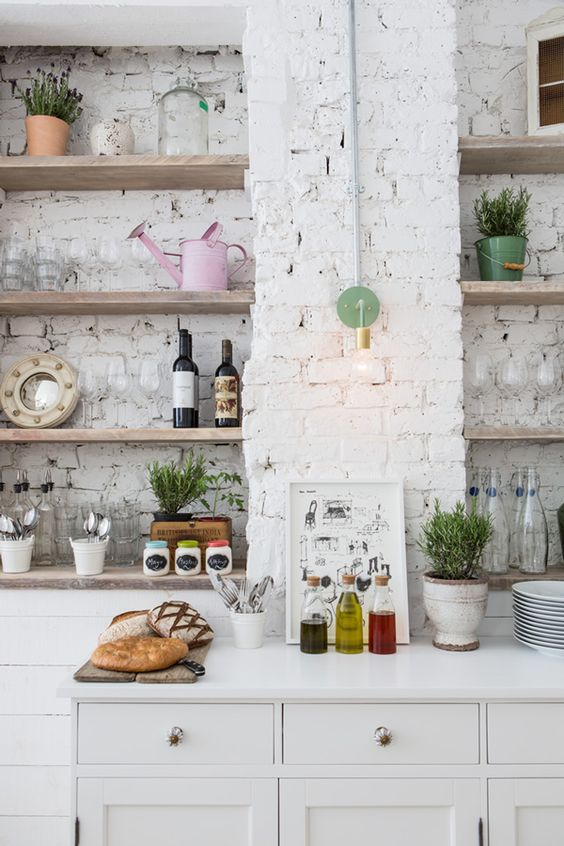 a Scandinavian kitchen done with white bricks that act as a backdrpo and even a backsplash