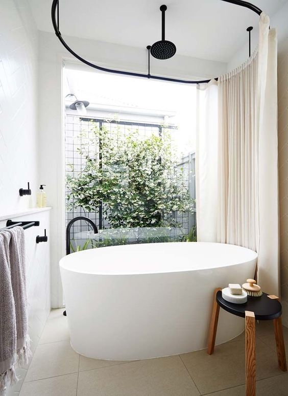 a contemporary bathroom with an oval tub and a view to the inner courtyard with much greenery