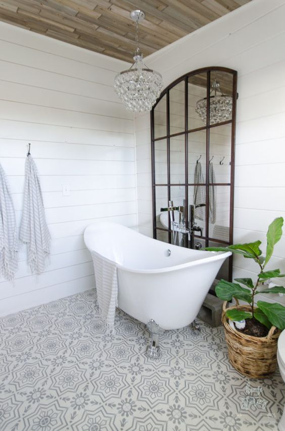a glam farmhouse bathroom done with white shiplap, mosaic tile floors and a crystal chandelier plus a framed mirror