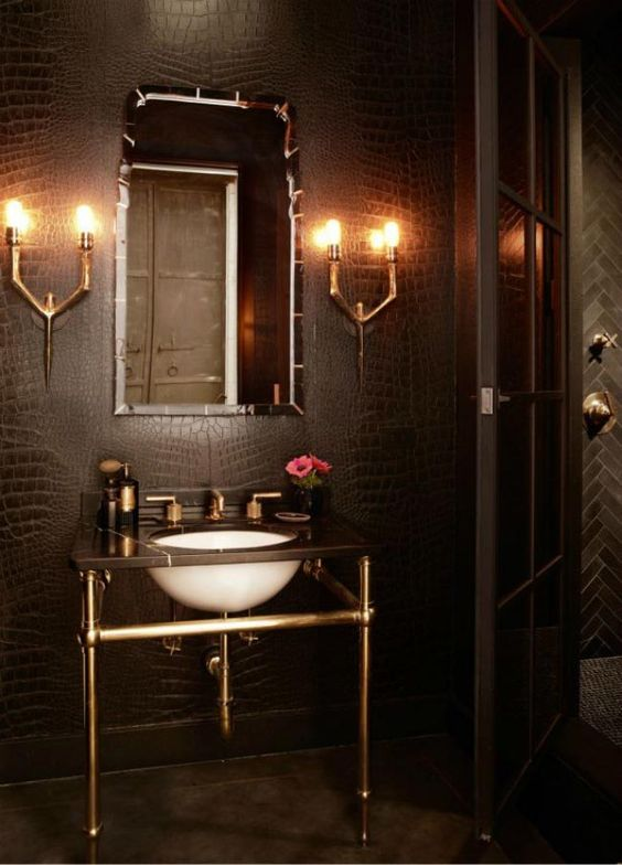 a small powder room lit up with wall lamps to make it brighter, fresher and more welcoming