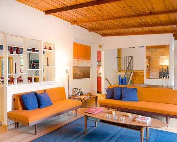 a super bright orange and blue living room calmed down with neutrals is a bold idea