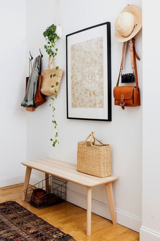 an artwork, a hanging planter with greenery and even a straw bag and hat add to the decor of the space