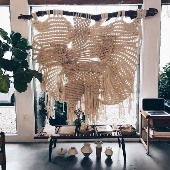 an oversized macrame hanging on a branch is a bold boho chic statement for any space