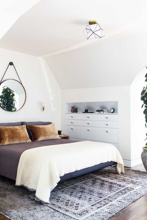 the bedroom is decluttered with some built-in storage units and additional negative space