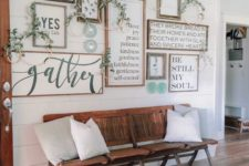 17 a cozy rustic gallery wall with greenery wreaths and decorative plates for a farmhouse entryway